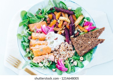 Vibrant Scandinavian lunch bowl with hot smoked salmon, spelt, root vegetables, rye bread, pickled onion and more