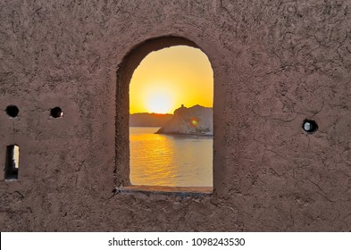 Vibrant sunrise silhouetting an old watchtower in the distance viewed through a curvy window surrounded by textured wall.