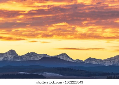 A vibrant sunset of brilliant orange and yellow lights the foothills of the Canadian Rockies outside the city of Calgary, Alberta, on a cold winter afternoon.