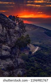 Vibrant sunset over the mountains of Samothrace Island in Greece with a road in the background and cliffs in the foreground