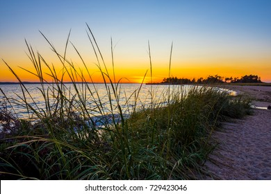 A vibrant sunset through the grass on Sandy Hook Bay along the New Jersey coastline.