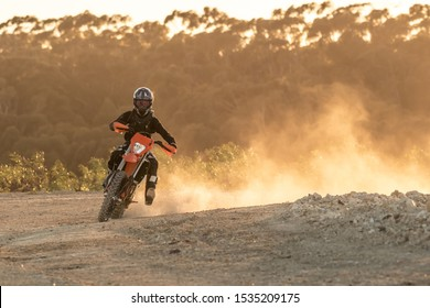 vibrant and warm image of a female enduro rider leaving a dust cloud on a dawn ride
