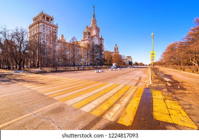 Vibrant wide angle view of long avenue of spring sunny campus of Moscow University with yellow zebra crossroad