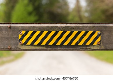 A vibrant yellow and black hazard no entry sign on a wooden gate post with a forest backdrop.