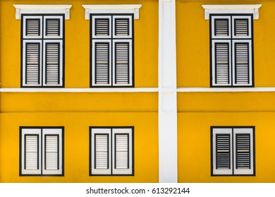 Vibrant yellow exterior building facade with windows