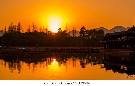 Vibrant yellow and orange sunset over West Lake in Hangzhou, China.  Sunset reflections in the water.