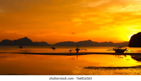 Vibrant yellow and orange sunsets over the horizon reflecting into the waters in El Nido, Palawan. Philipines