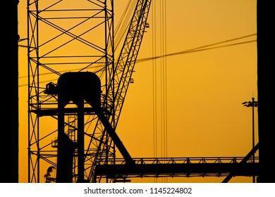 Vibrant yellow sunset above the sea port in Poti, Georgia. Construction crane.