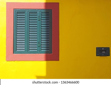 a vibrant yellow wall with red frame and green closed shuttered window typical Portuguese colors in bright sunlight and shade with space for copy