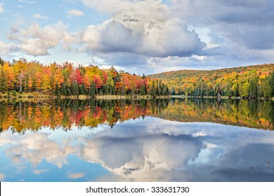 Vibrantly colorful fall foliage and white clouds in a blue sky are reflected on Lake Plumbago at Alberta in Upper Peninsula Michigan.