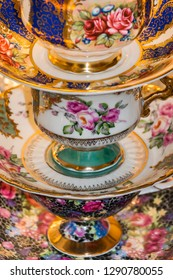 A vibrantly coloured, mismatched, stack of vintage china cups and saucers.