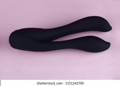 Vibrator sex toy for adult, design minimal dildo vibrator for clitoris and anal pleasure isolated on pink background.