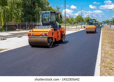 Vibratory asphalt roller compactor on site, compacting new asphalt pavement in urban modern city
