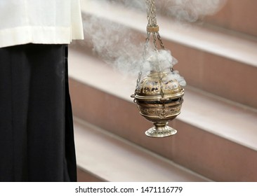 A vicar is swinging a silver censer to burn incence during church service, Brunswick, Germany 2017