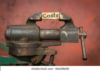 Vice tool squeezing the word. Costs reduction concept