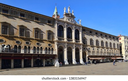 Vicenza, Italy - October 2, 2018: People walk along a historical palazzo with shops on the Piazza dei Signori in Vicenza, Italy on October 2, 2018