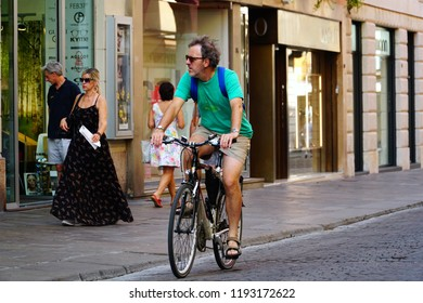 Vicenza/Veneto/Italy - 4 August 2018: Italian lifestyle. Italian man rides the bike, street as background. Bicycle is the popular personal transport for Italian people. View of the city of Vicenza.