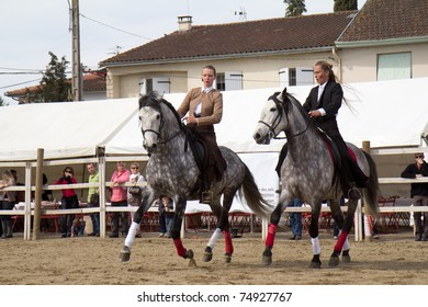 """VIC-FEZENSAC, FRANCE, APRIL 2: Two unidentified female riders on gray horses display their riding skills at the locally organized """" La foire aux chevaux de printemps"""" fair on April 2, 2011, in Vic-Fezensac, France."""
