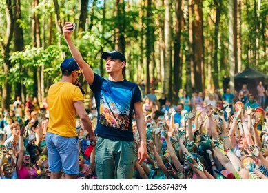 VICHUGA, RUSSIA - JUNE 17, 2018: Man takes a selfie on the phone against the crowd to celebrate the festival of colors Holi