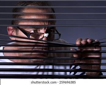 Vicious man looking sideways through venetian blind