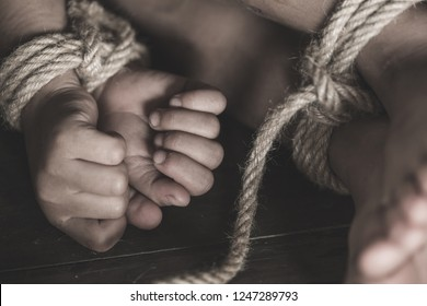 Victim boy with hands tied up with rope in emotional stress and pain,  kidnapped, abused, hostage,  afraid, restricted, trapped,  struggle,  Stop violence against children and trafficking Concept.