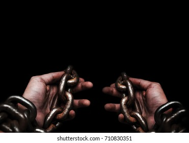 Victim, Slave, Prisoner male hands tied by big metal chain by him self. People have no freedom concept image.