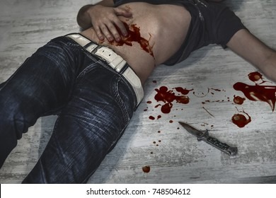 A victim of a violent crime lies in an apartment. The Young man's body in a bloody wound lying on the dirty floor next to a bloody knife. Cold weapon. The victim of a violent crime