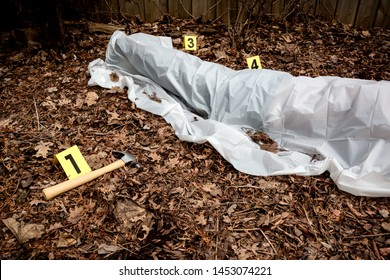 Victim of a violent crime under a sheet in a rural yard. With evidence markers and a hammer murder weapon.
