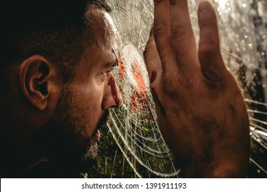 Victim of war. Wounded man victim looking through broken glass. Crime or violence victim. Victim of accident.