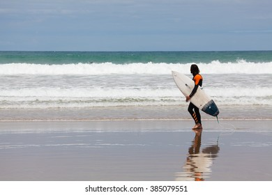 Victoria, Australia - November 22, 2015: View of surfer walking along the beach in Torquay, one of the most popular places to go surfing on the Great Ocean Road, during daytime.