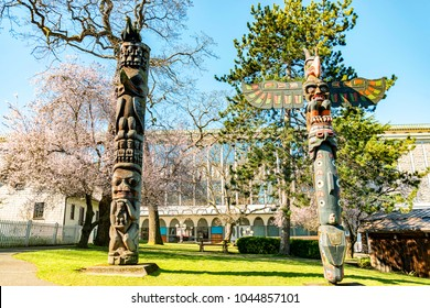 Victoria, BC, Canada - 11 March 2018. Beautiful totem pole  in Thunderbird totem poles park with cherry bloom. Totem poles made by  indigenous Canadians. The park located near the Royal BC Museums.