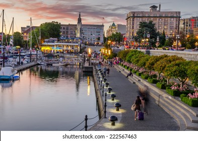 Victoria, BC, Canada - July 4, 2014: Inner Harbour pathway at Sunset crowded with people in motion. This patch of waterfront is the location of many tourist attractions and recreational activities.