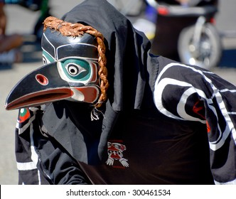 VICTORIA BC CANADA JUNE 24 2015: Native Indian man in traditional costume and wooden mask. First Nations in BC constitute a large number of First Nations governments and peoples in the province of BC