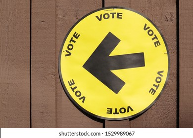 Victoria, BC, Canada - October 13 2019: Canadian Federal Election circular yellow sign with the word vote and an arrow pointing to the left on a painted board and batten wall