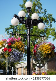 Victoria, British Columbia, Canada hanging flower baskets on street lights.  Decorative street lamps with five white globes are a landmark in Victoria in summer.  Government building in background