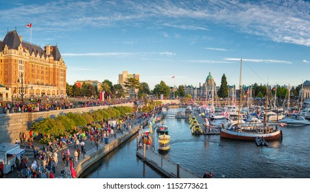 Victoria, British Columbia / Canada - July 1, 2018: Masses of people visiting the celebrations for Canada Day at inner harbour with the parliament building during sunset.