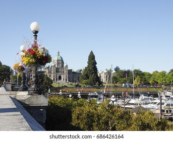 Victoria British Columbia Canada on Vancouver Island.  View of Legislature, Inner Harbor with iconic globe streetlight and hanging flower baskets in summer.  Victoria is the capital city of BC