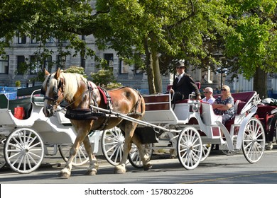 Victoria, British Columbia / Canada - September 5 2019:  Tourist Couple Riding in a Horse Drawn Carriage taking a Tour of the City