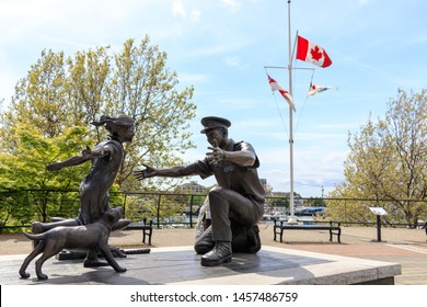 "VICTORIA, CANADA - May 3, 2019: ""The Homecoming"" Statue, waterfront in downtown Victoria, BC on sunny day with waving Canadian flag in the background,"