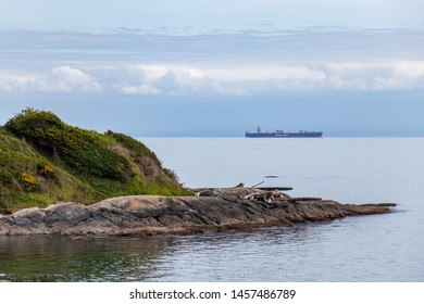 VICTORIA, CANADA - May 3, 2019: Hapag Lloyd container ship seen out in the distance from Holland Point Park in Victoria, BC.