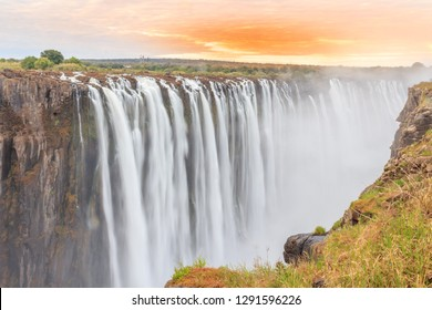 Victoria Falls, a waterfall in southern Africa on the Zambezi River at the border between Zambia and Zimbabwe. Milky water & orange clouds