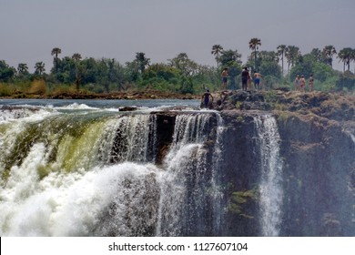 VICTORIA FALLS, ZIMBABWE - CIRCA OCTOBER 2016: Tourists in the Devil's Pool above Victoria Falls, seen from the Zimbabwe side