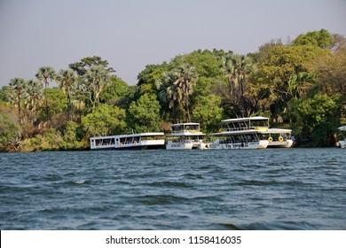 VICTORIA FALLS, ZIMBABWE - CIRCA OCTOBER 2016: Pontoon tour boats on the Zambezi River