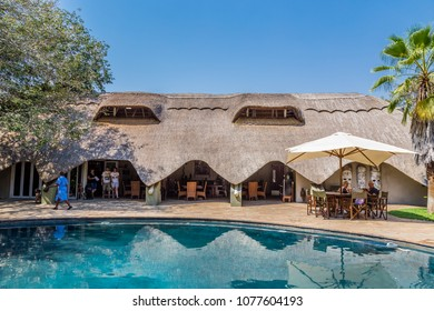 Victoria Falls, Zimbabwe, September, 6, 2016: Bayete Lodge. The thatched dining room of Bayete Lodge beside the swimming pool.