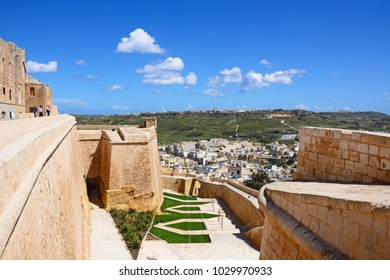VICTORIA, GOZO, MALTA - APRIL 3, 2017 - Elevated view of buildings and landscaped moat within the citadel with tourists enjoying the sights, Victoria (Rabat), Gozo, Malta, April 3, 2017.