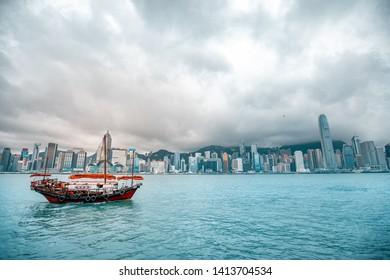 Victoria Harbor, Hong Kong - June 02, 2019 : Traditional chinese junk boat passing the Victoria Harbor.