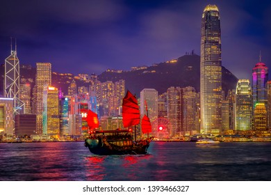 Victoria Harbor Hong Kong night view with tourist sailboat at night. View from across Victoria Harbor Hong Kong.