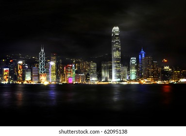 Victoria harbor in illuminated at nighttime with futuristic buildings and colorful lights.