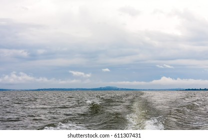 Victoria Lake with wave from motorboat and hazy land in horizon against overcast morning sky background. Entebbe, Uganda, Eastern Africa.