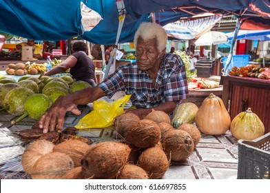 Victoria, Mahe, Seychelles - December 16, 2015: Sellers offer fresh fruits in the Sir Selwyn Selwyn Clarke Market. Built in 1840 and renovated in 1999.
